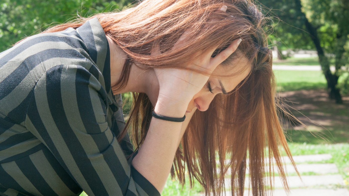 Depressed girl sitting on bench in park. Side view of frustrated young woman with closed eyes covering ears with hands and holding head. Depressive syndrome concept