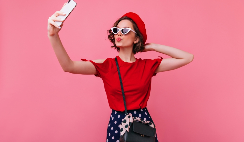 Confident french woman posing with kissing face expression. Studio shot of lovely female model in red beret expressing love while making selfie.